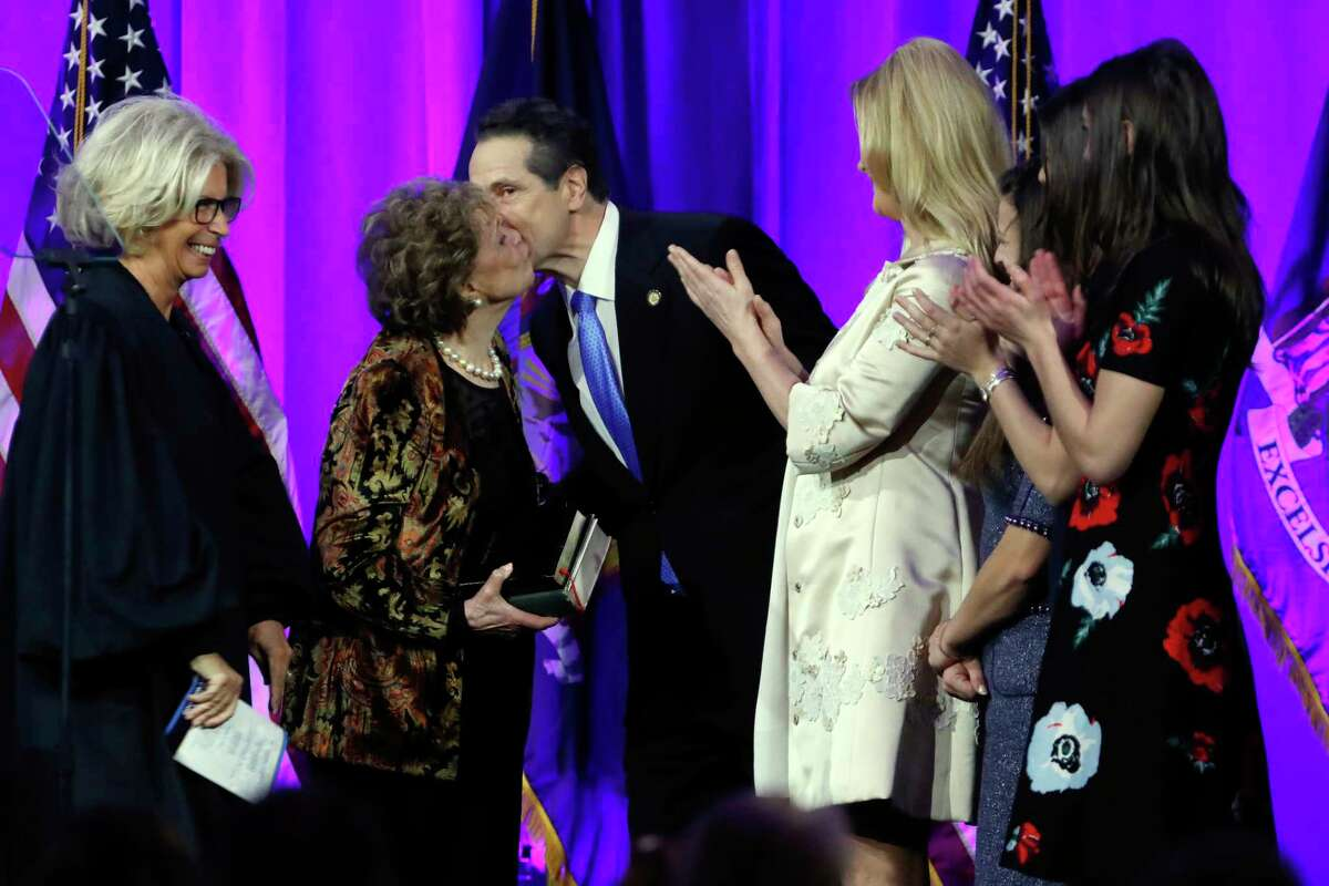 New York Gov. Andrew Cuomo gets a kiss from his mother Matilda Cuomo after his third oath of office, on Ellis Island in New York harbor, Tuesday, Jan. 1, 2019.