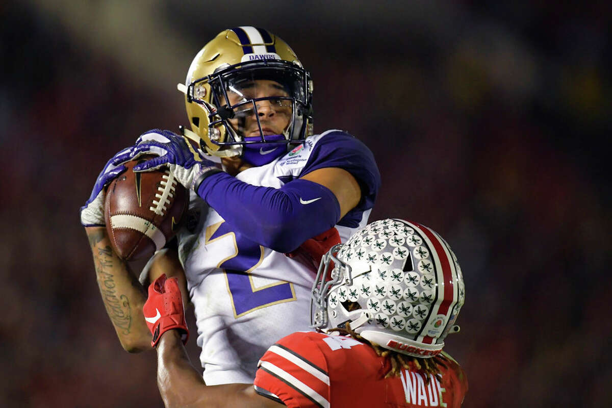 Washington wide receiver Aaron Fuller catches a pass over Ohio State cornerback Shaun Wade during the second half of the Rose Bowl NCAA college football game Tuesday, Jan. 1, 2019, in Pasadena, Calif. (AP Photo/Mark J. Terrill)