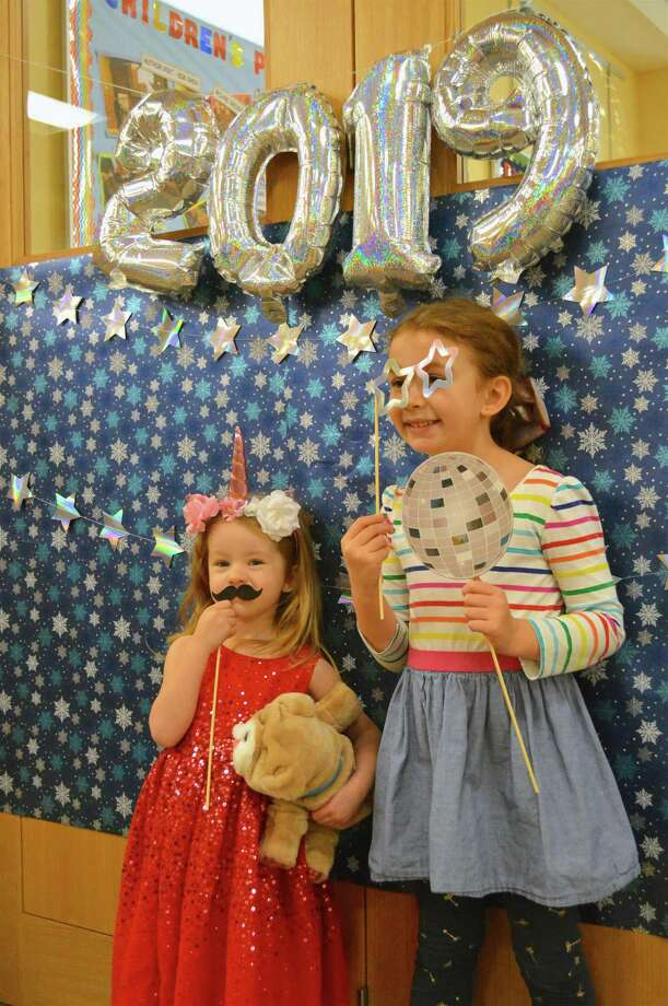 "Willa Gwin, 2, left, of Darien, and her sister, Poppy, 5, pose for a picture at the ""Noon"" Year's Eve celebration at Darien Library, Monday, Dec. 31, 2018, in Darien, Conn. Photo: Jarret Liotta / For Hearst Connecticut Media / Darien News Freelance"