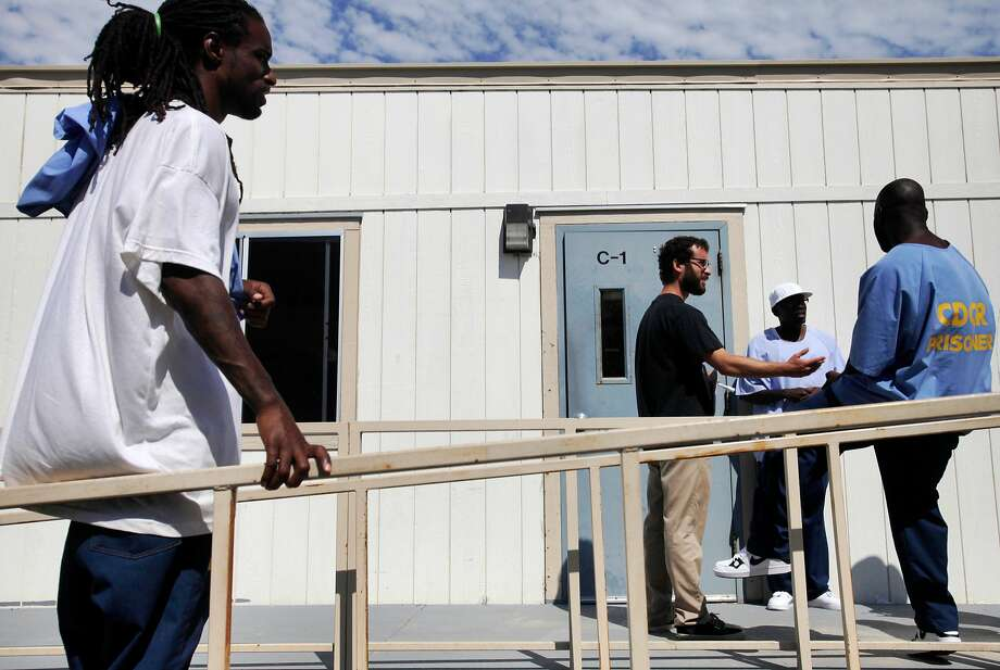Students, from front left, Timothy Nash, 35, Kinte Hogan, 37, and Cleo Cloman, 37, chat with their teacher, Berkeley Graduate student Jake Martin Grumbach, 26, second from left, as they take a break during a US History 102 class through the Prison University Project at the San Quentin State Prison July 29, 2014 in San Quentin, Calif. The Prison University Project initially formed in 2003 to help provide materials, financial and administrative support for the existing College Program. In 2006 the Prison University Project became an independent non-profit and today they provide College Prep and Associate of Arts Degree programs to hundreds of students every year. Photo: Leah Millis / The Chronicle