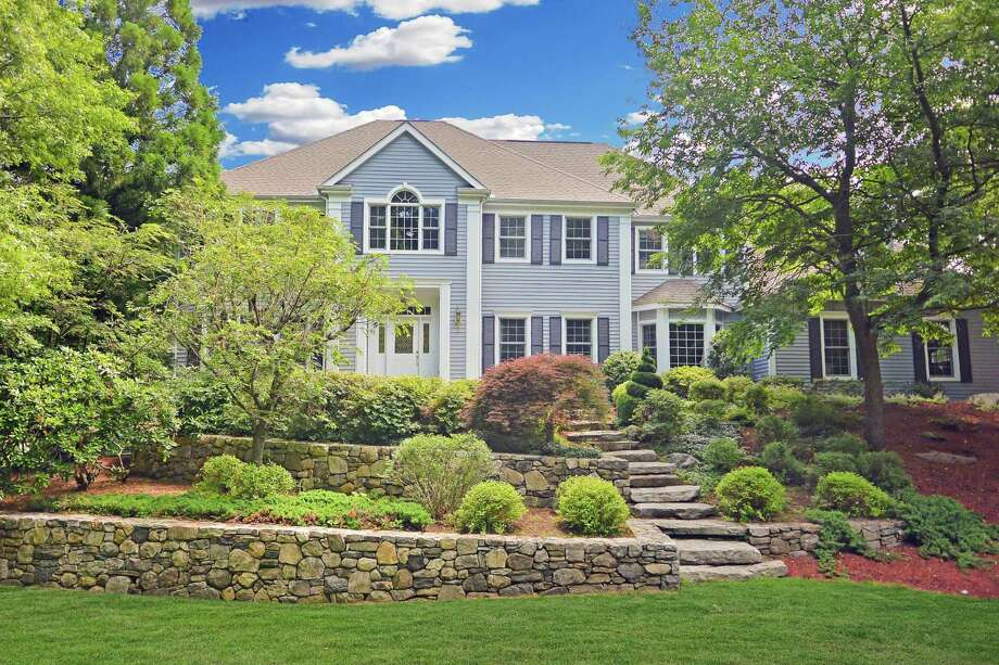 The custom-built colonial house at 92 Turtlehead Road sits in a private association on a one-acre property that abuts the Weir Preserve.