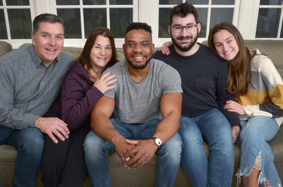Jean Pierre Clarke, center, with the Lamason family, Dave, Lisa, Troy and Zoe, at their home Friday, December 28, 2018, in Wilton, Conn. J.P. Clarke originally came to Wilton as a scholar in A Better Chance of Wilton (ABC) program in 2010 to live with Lisa Lamason and his host family. After receiving a scholarship to Notre Dame University where he studied Aerospace Engineering he interned at ASML in Wilton, was later hired by ASML, and went back to live with the Lamason family. Photo: Erik Trautmann / Hearst Connecticut Media / Norwalk Hour