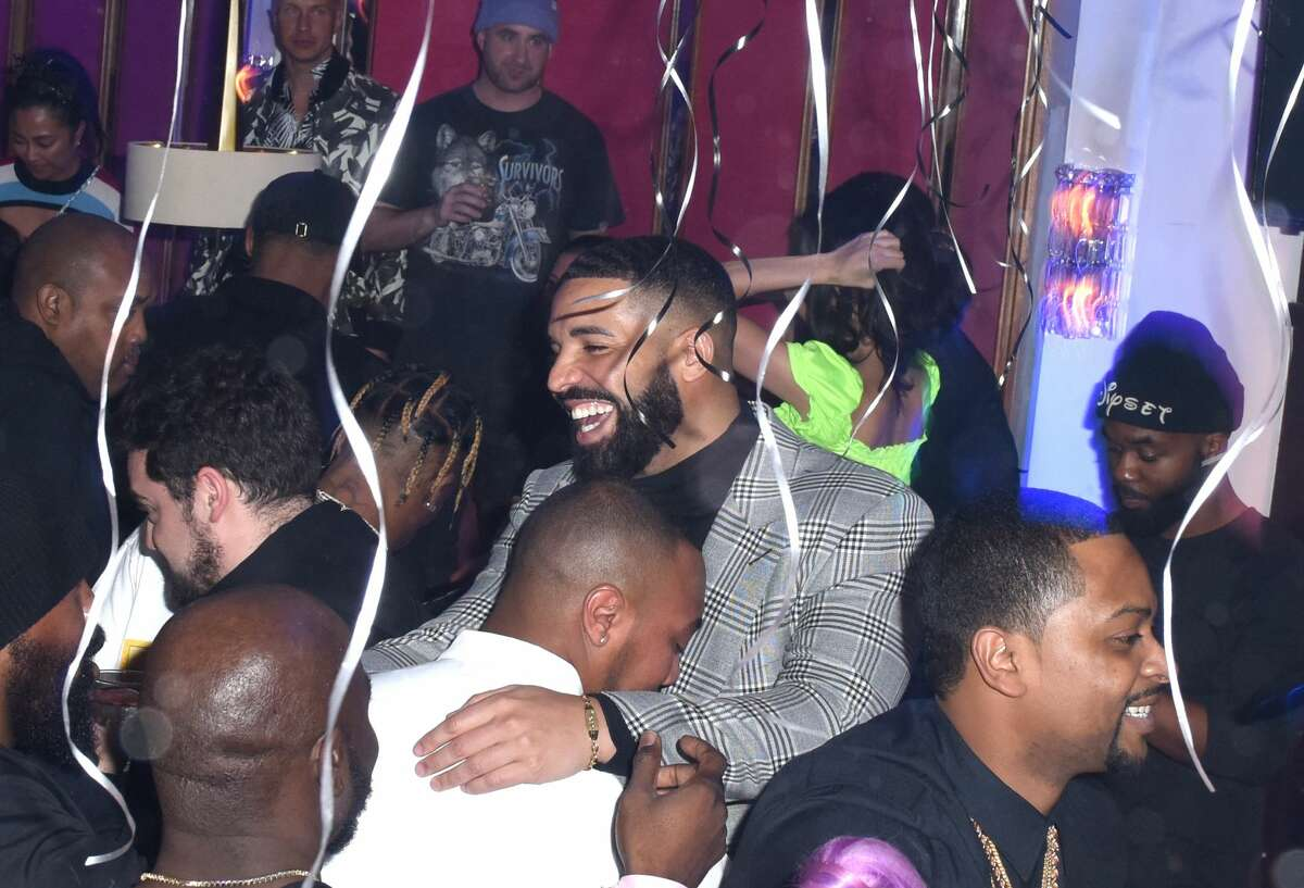 Drake mingles at the Mod Selection Champagne party. Kendall Jenner, in the green shirt, attended with her reported beau Ben Simmons of the Philadelphia 76ers. (Photo by Vivien Killilea/Getty Images for The h.wood Group)