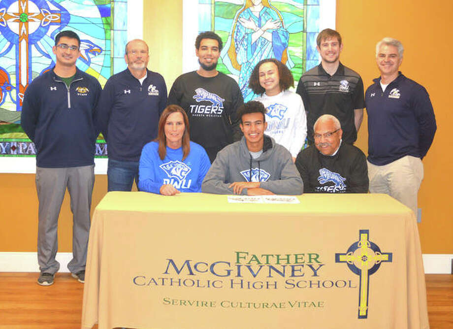 Father McGivney senior Elijah Burns signed with Dakota Wesleyan University for cross country and track and field. In the front row, from left to right, are mother Julie Gary, Elijah Burns and grandfather Louis Gary. In the back row, from left to right, are FMCHS athletic director Jeff Oller, FMCHS cross country and track and field coach Jim Helton, brother Isaiah Burns, sister Jordan Gary, Dakota Wesleyan cross country coach Jamen Helton and FMCHS principal Joe Lombardi. Photo: Scott Marion/Intelligencer
