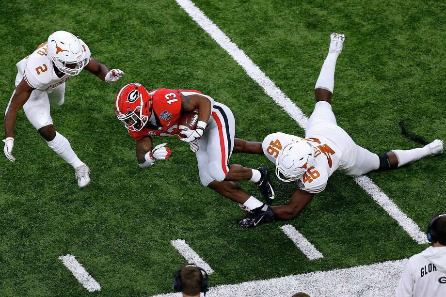 Elijah Holyfield (13) of the Georgia Bulldogs is tackled by Joseph Ossai (46) of the Texas Longhorns during the first half of the Allstate Sugar Bowl at the Mercedes-Benz Superdome on January 01, 2019 in New Orleans, Louisiana. Photo: Jonathan Bachman, Stringer / Getty Images / 2019 Getty Images