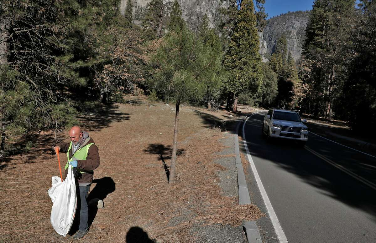 Volunteer Mark Ruter, places some trash he found in a bag as he helps the group Facelift clean up Yosemite during a partial government shutdown that has Yosemite National Park without key services including trash removal and some bathroom services in Yosemite, Calif., on Wednesday, January 2, 2019.