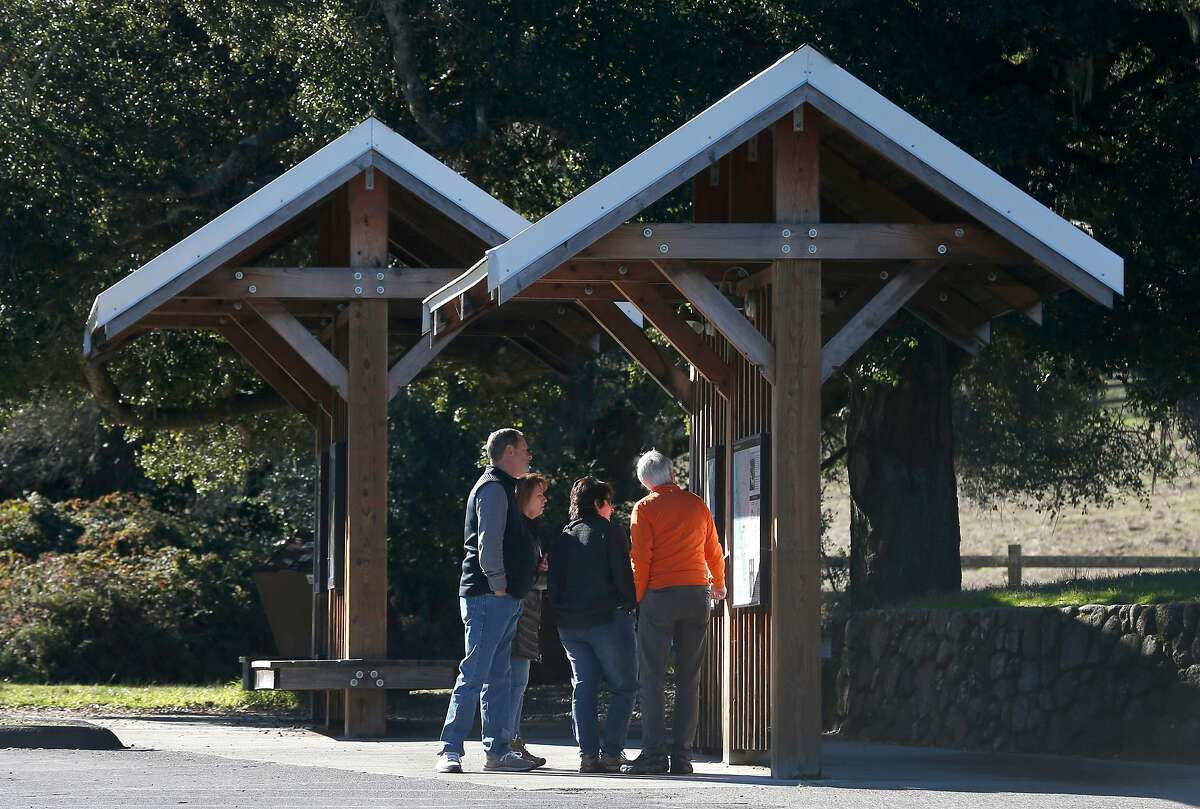 Larry Shuster and Cheryl Hall study a trail map posted on a kiosk with Clint and Colleen Schmitt at the Point Reyes National Seashore visitor center in Olema, Calif. on Wednesday, Jan. 2, 2019.