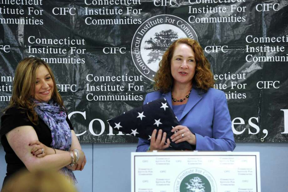 Monica Bevilacqua, left, Head Start director in Danbury, Conn, and U.S. rep Elizabeth Esty, who is presenting her with a flag that had flown at the Capital in Washington, D.C. Photo: Carol Kaliff / Carol Kaliff / The News-Times