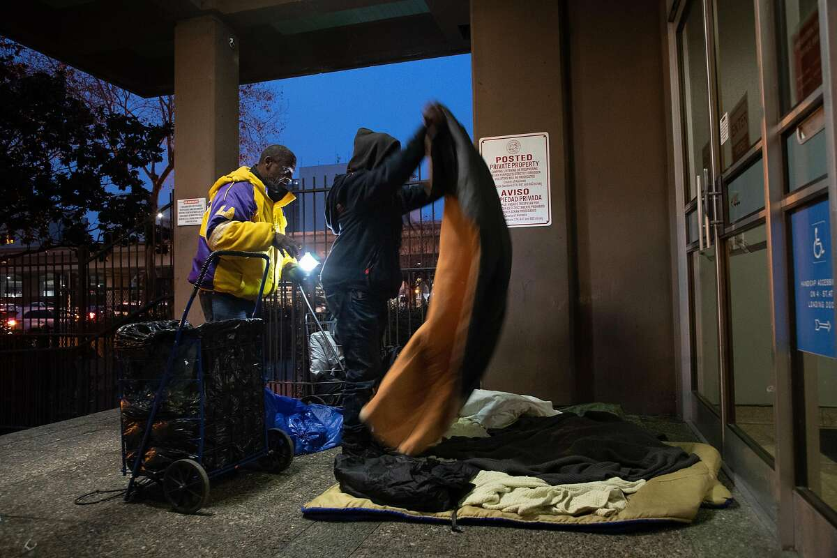 Gregory Dunston Sr. and Marie McKenzie set up their bed at a downtown building on Thursday, Dec. 20, 2018, in Oakland, CA.