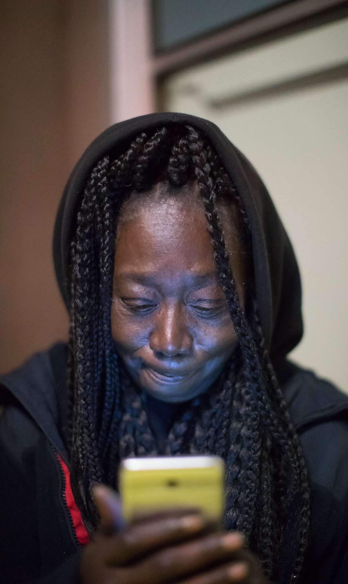 Marie McKinzie looks at her phone before going to sleep on Thursday, Dec. 20, 2018, in Oakland, Calif.