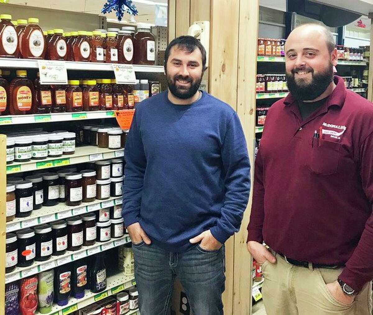 FILE - Brett McCoy (left) and McDonald's Food and Family Center employee Ryan Tenbusch, stand next to a brand new display of McCoy Honey, sitting on the top shelf at the store in 2019. (Courtesy Photo)