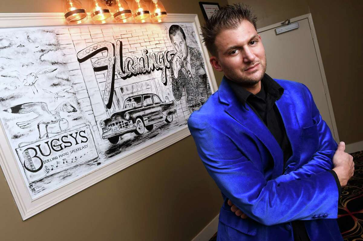 Pauly Popolizio is photographed by one of his paintings displayed in the entryway to Bugsy's Dueling Piano Speakeasy in Hamden.