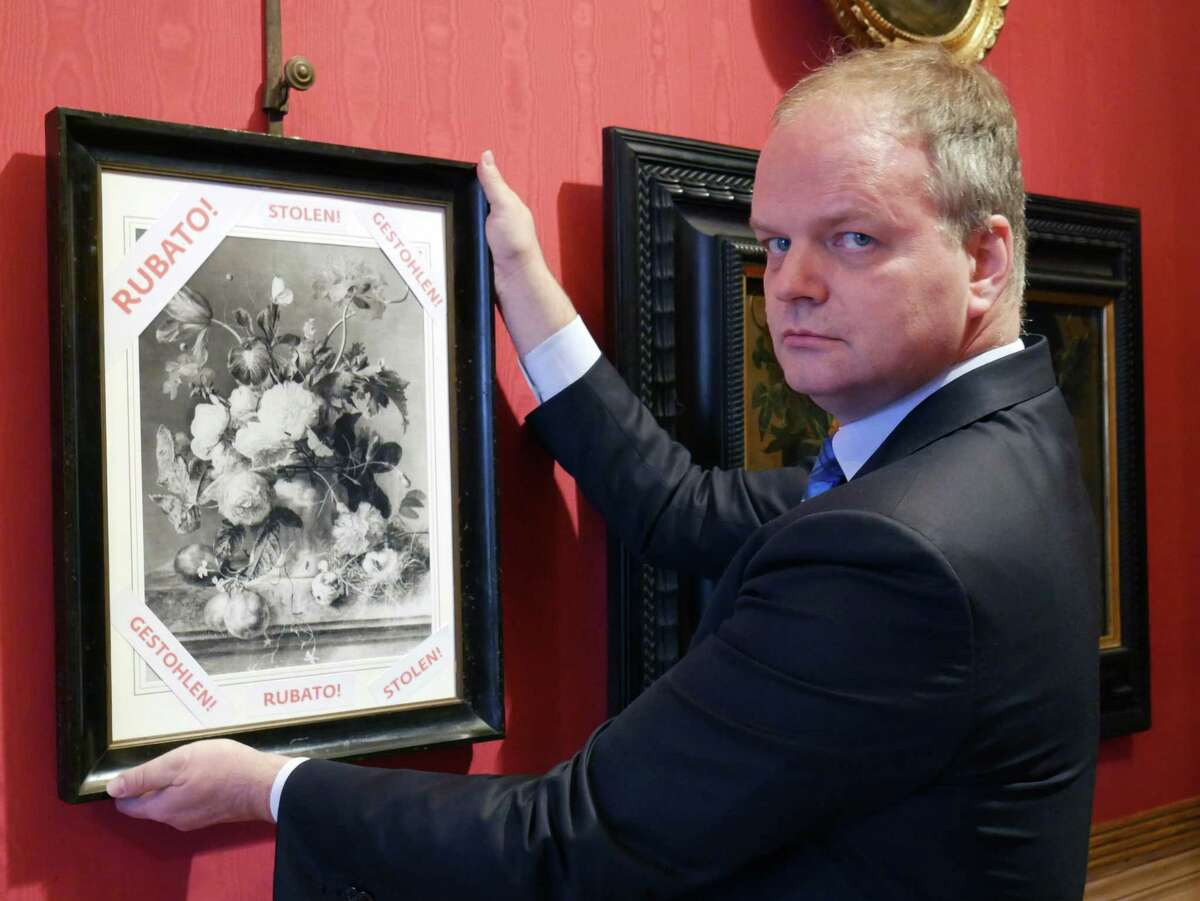 """Eike Schmidt, director of the Uffizi Gallery, holds onto a copy of a still-life """"Vase of Flowers"""", by Dutch artist Jan van Huysum, with writing in red reading """"stolen,"""", inside the gallery in Florence, Italy."""