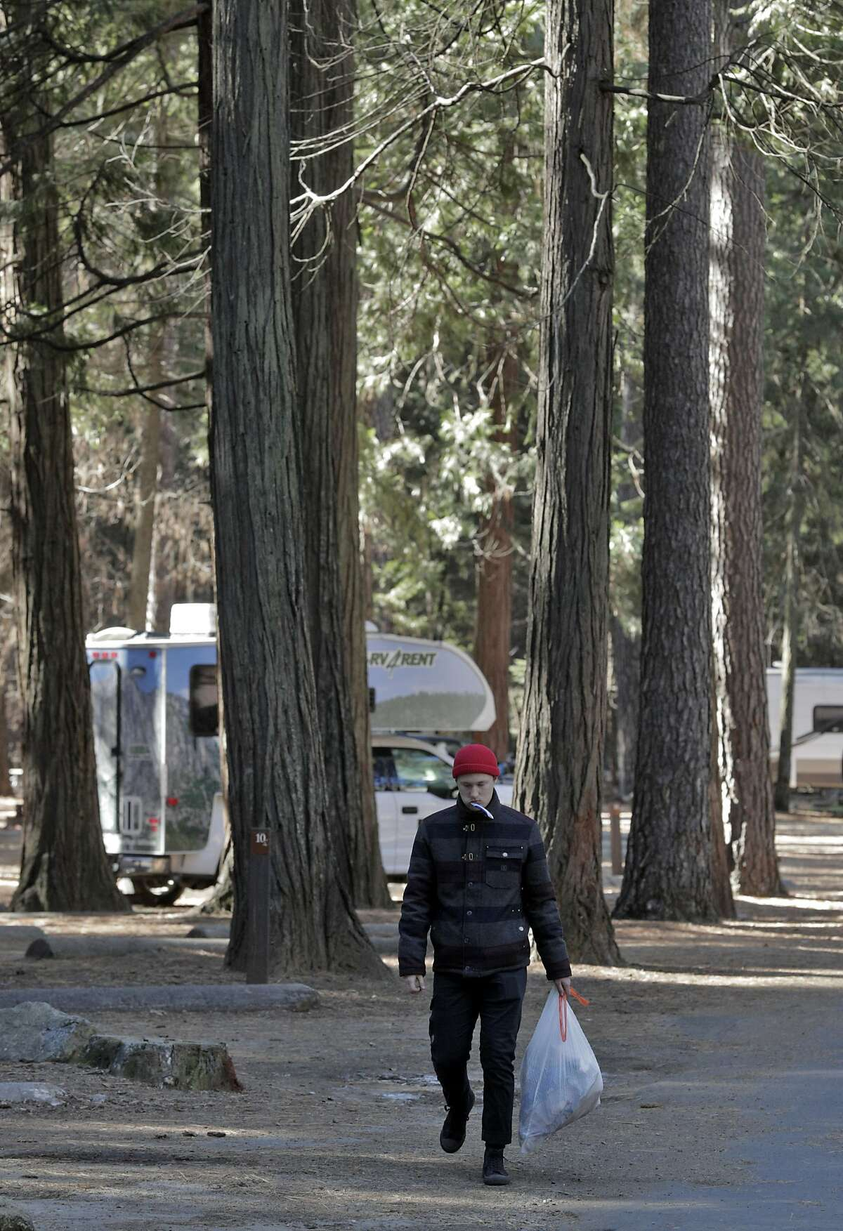Seth Williams from Costa Mesa carries his garbage to a trash can in Upper Pines Campground, the only one open in Yosemite, during a partial government shutdown that has Yosemite National Park without key services including trash removal and some bathroom services in Yosemite, Calif., on Wednesday, January 2, 2019.
