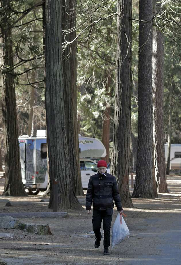 Seth Williams from Costa Mesa carries his garbage to a trash can in Upper Pines Campground, the only one open in Yosemite, during a partial government shutdown that has Yosemite National Park without key services including trash removal and some bathroom services in Yosemite, Calif., on Wednesday, January 2, 2019. Photo: Carlos Avila Gonzalez / The Chronicle