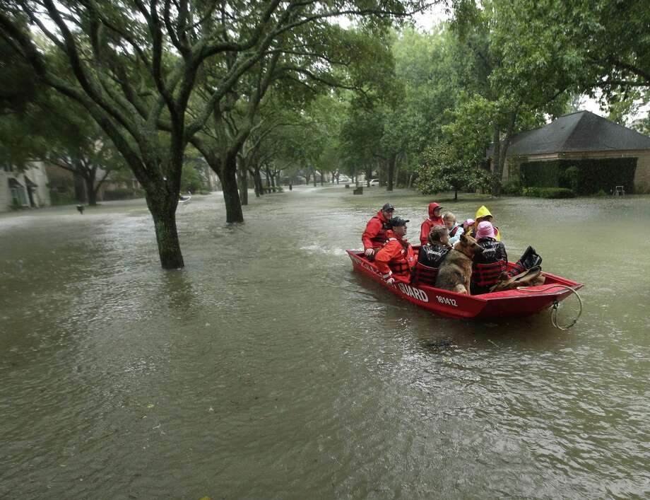 FILE - In this Aug. 28, 2017, file photo, a Coast Guard rescue team evacuates people from a neighborhood inundated by floodwaters from Tropical Storm Harvey in Houston, Texas. Natural disasters in Texas on the scale of Hurricane Harvey's deadly destruction last year will become more frequent because of a changing climate, warns a new report Thursday, Dec. 13, 2018, ordered by Republican Gov. Greg Abbott in a state where skepticism about climate change runs deep. (AP Photo/Charlie Riedel, File) Photo: Charlie Riedel, STF / Associated Press / Copyright 2018 The Associated Press. All rights reserved.