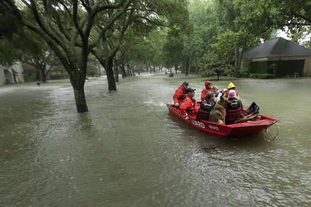 FILE - In this Aug. 28, 2017, file photo, a Coast Guard rescue team evacuates people from a neighborhood inundated by floodwaters from Tropical Storm Harvey in Houston, Texas. Natural disasters in Texas on the scale of Hurricane Harvey?'s deadly destruction last year will become more frequent because of a changing climate, warns a new report Thursday, Dec. 13, 2018, ordered by Republican Gov. Greg Abbott in a state where skepticism about climate change runs deep. (AP Photo/Charlie Riedel, File)