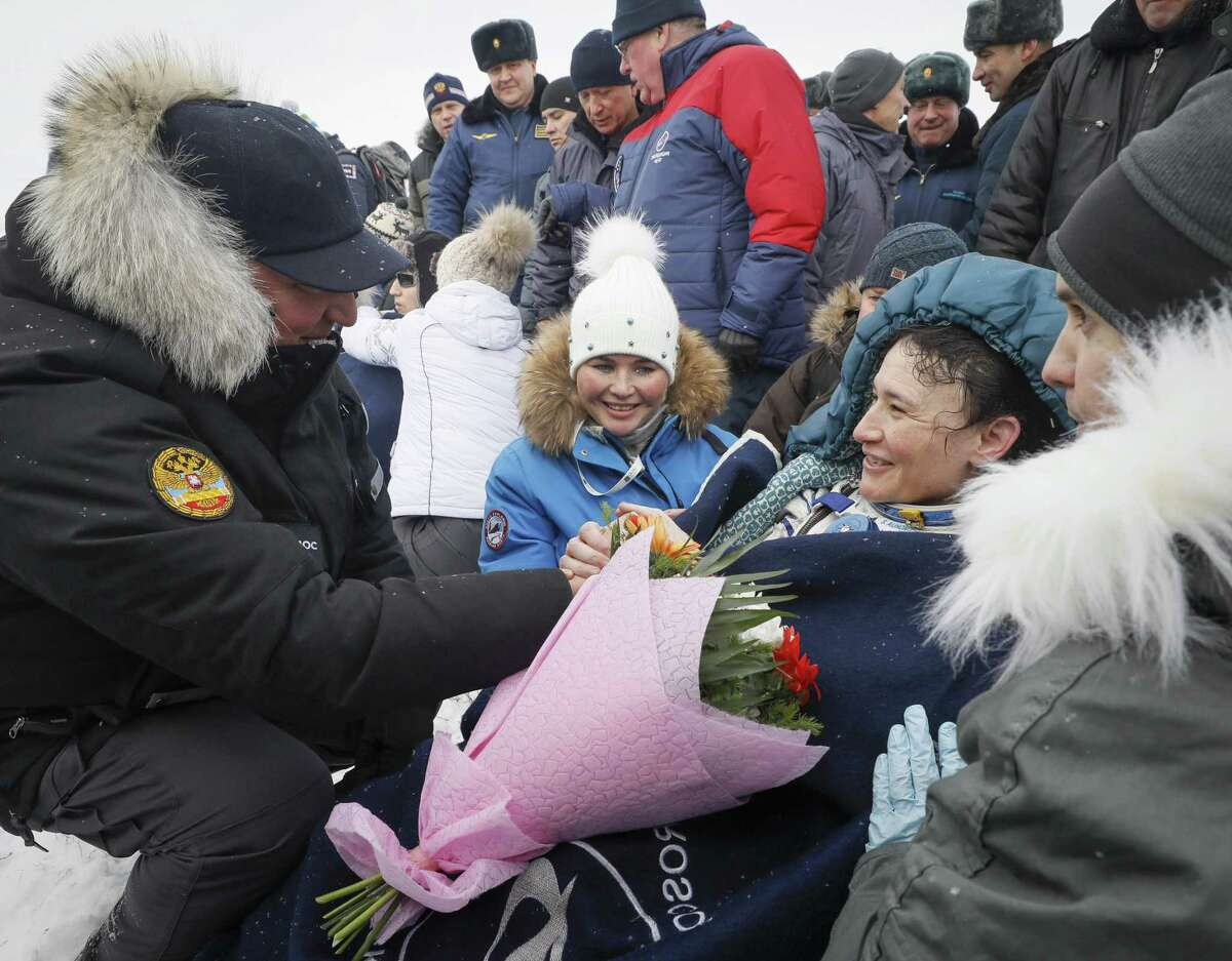Dmitry Rogozin, head of the Russian space agency Roscosmos, presents flowers to NASA'ss Serena Aunon-Chancellor after landing in a remote area outside the town of Zhezkazgan, formerly known as Dzhezkazgan, Kazakhstan, on Thursday, Dec. 20, 2018. Three astronauts have returned to Earth after more than six months aboard the International Space Station. (