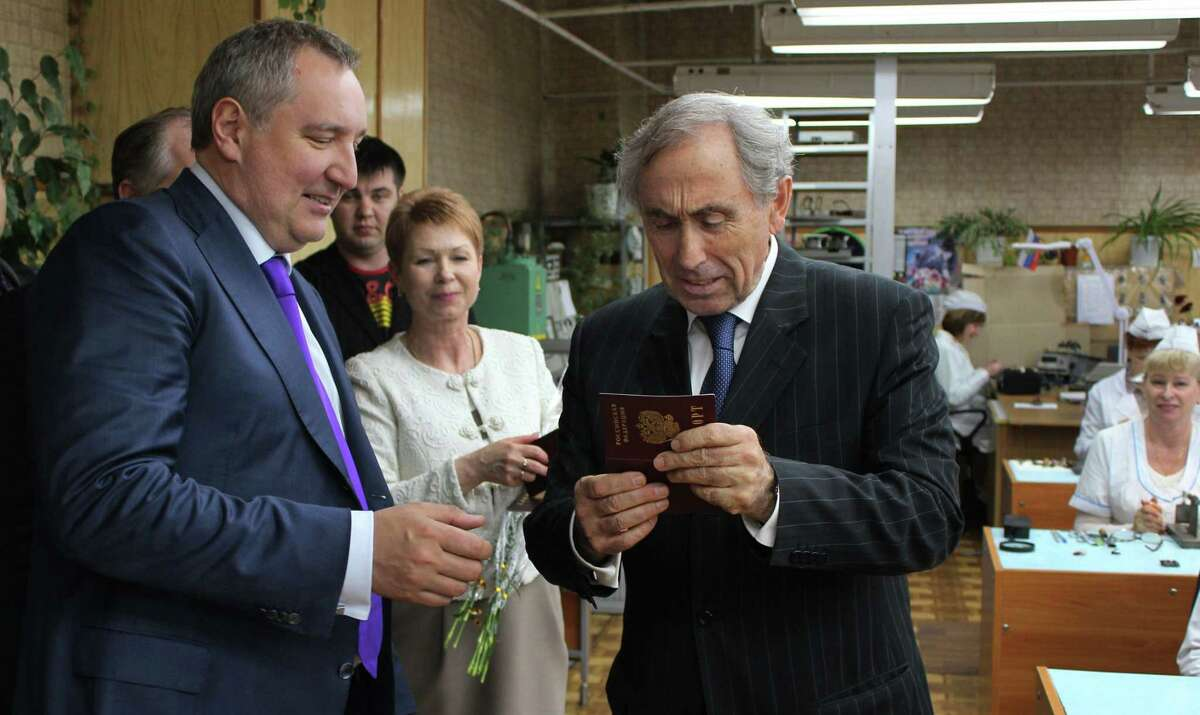 In this April 2014 file photo, Russia's then deputy prime minister Dmitry Rogozin, left, hands over a Russian passport to an employee of the Fiolent Radio Parts Factory in the Crimean capital Simferopol.