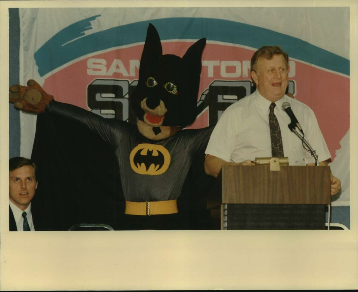 San Antonio Spurs draft, Arena; Red McCombs, owner, addresses crowd with thelp of Coyote mascot dressed as Batman; broadcaster Dave Barrett at left; NBA basketball 1989