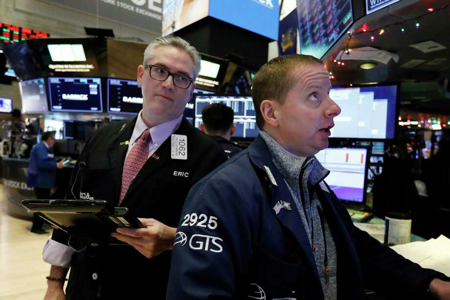 Trader Eric Schumacher, left, and specialist Robert Nelson work on the floor of the New York Stock Exchange, Wednesday, Jan. 2, 2019. Stocks are coming off their worst year in a decade as investors worry about slowing global economic growth and trade tensions between the U.S. and China. (AP Photo/Richard Drew) Photo: Richard Drew / Copyright 2018 The Associated Press. All rights reserved