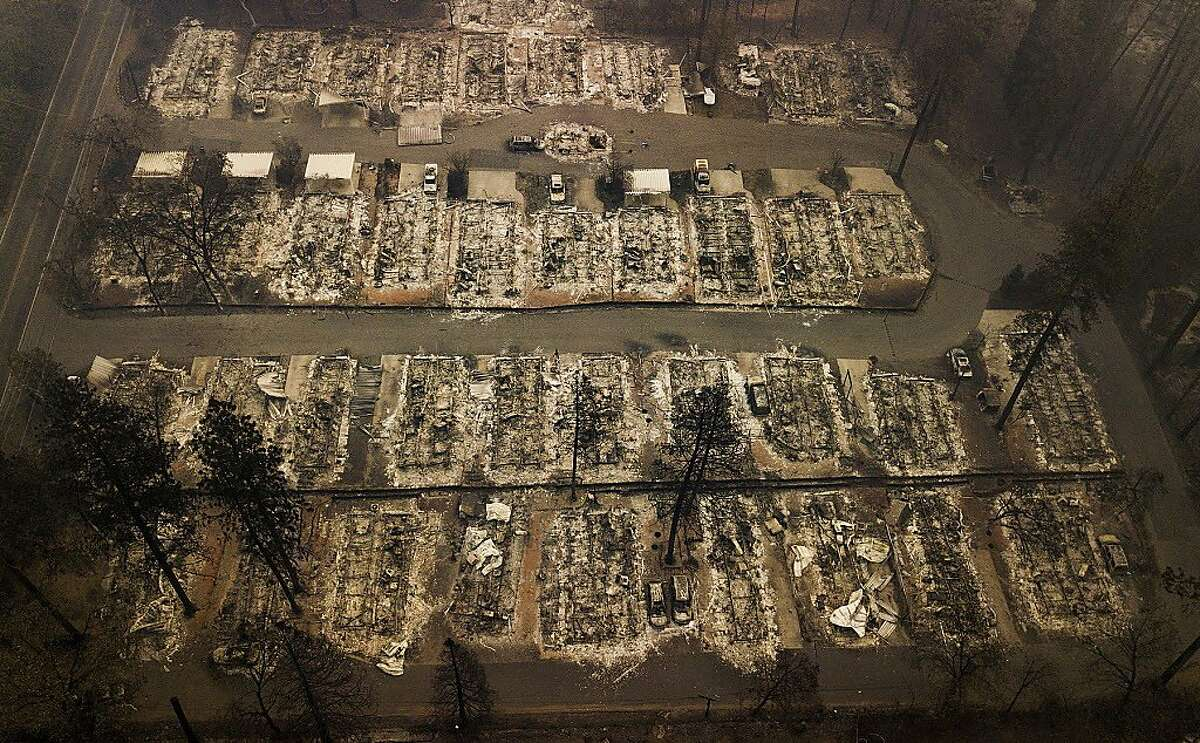 FILE - This Thursday, Nov. 15, 2018, file aerial photo shows the remains of residences leveled by the wildfire in Paradise, Calif. California's attorney general has told a federal judge it's possible Pacific Gas & Electric Co. could face charges up to murder if investigators find reckless operation of power equipment caused any deadly wildfires in the past two years. The Sacramento Bee reports the brief is purely advisory and any criminal charges would most likely be filed by county district attorneys. (AP Photo/Noah Berger, File)