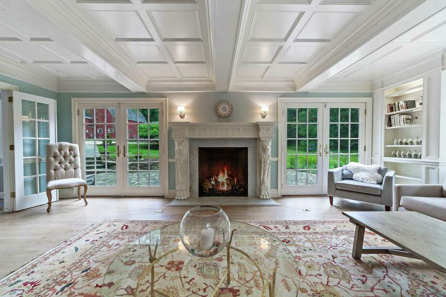 The elegant living room at 400 Burr St. in Fairfield is rich in trim and craftsmanship, highlighted by a coffered ceiling and fireplace with ornate mantel carved with scrolls, lion heads and medallions, forming the focal point of the room. Photo: The Vanderblue Team, Higgins Group / ONLINE_CHECK