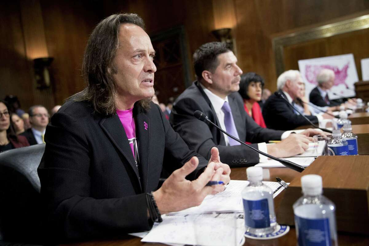 John Legere, chief executive officer of T-Mobile US Inc., speaks as Marcelo Claure, chief executive officer of Sprint Corp., center, listens during a Senate Judiciary Subcommittee hearing on the impact of the T-Mobile and Sprint transaction in Washington, D.C., U.S., on Wednesday, June 27, 2018. Legere told lawmakers Wednesday his company's proposed purchase of Sprint Corp. will bring lower prices, while a former U.S. antitrust official said the deal poses dangers from less competition.