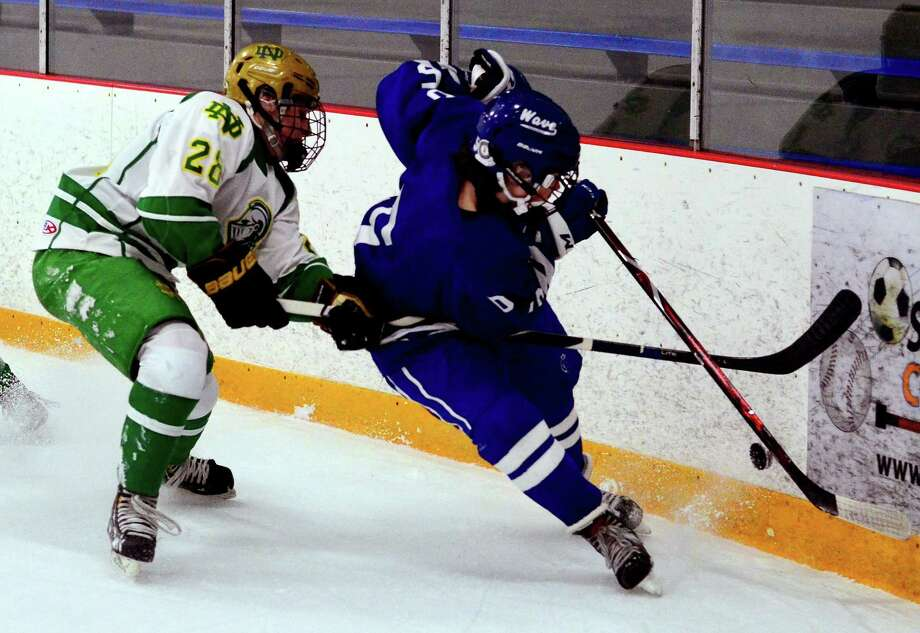 Darien's Teddy Dyer (5) and Notre Dame of West Haven's Ryan Ahearn (28), left, converge on the puck during boys hockey action in West Haven, Conn., on Wednesday Jan. 2, 2019. Photo: Christian Abraham / Hearst Connecticut Media / Connecticut Post