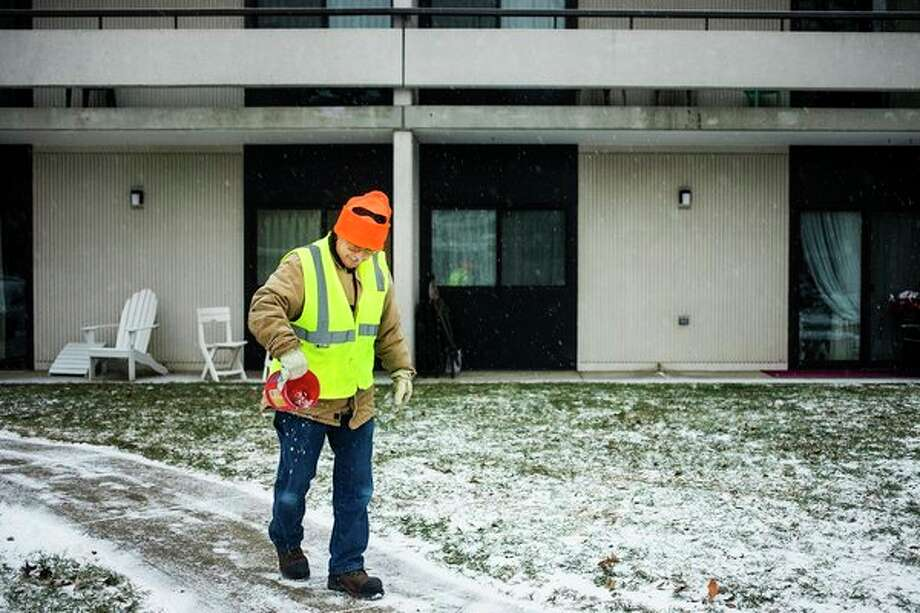 Val Burton spreads salt over a sidewalk in front of Washington Woods senior living center as snow continues to fall on Wednesday afternoon in Midland. (Katy Kildee/kkildee@mdn.net)