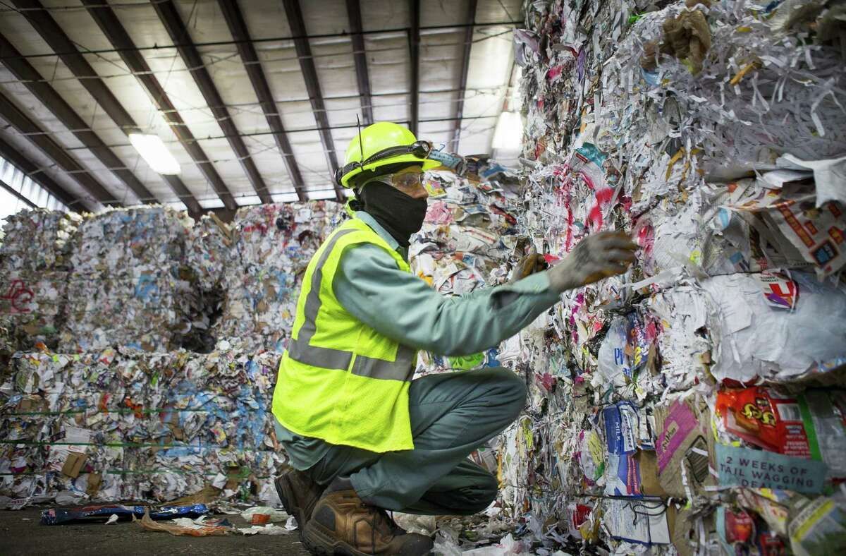 A Waste Management employee removes plastic, which accidentally made it through the sorting process, from a bale of mixed paper that is being prepared to be loaded onto a truck at the company's facility on Gasmer Drive in southwest Houston, Monday, Nov. 19, 2018.