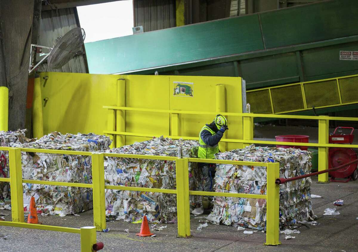 A Waste Management employee inspects bales of mixed paper that are being prepared to be loaded onto trucks at the company's facility on Gasmer Drive in southwest Houston, Monday, Nov. 19, 2018.