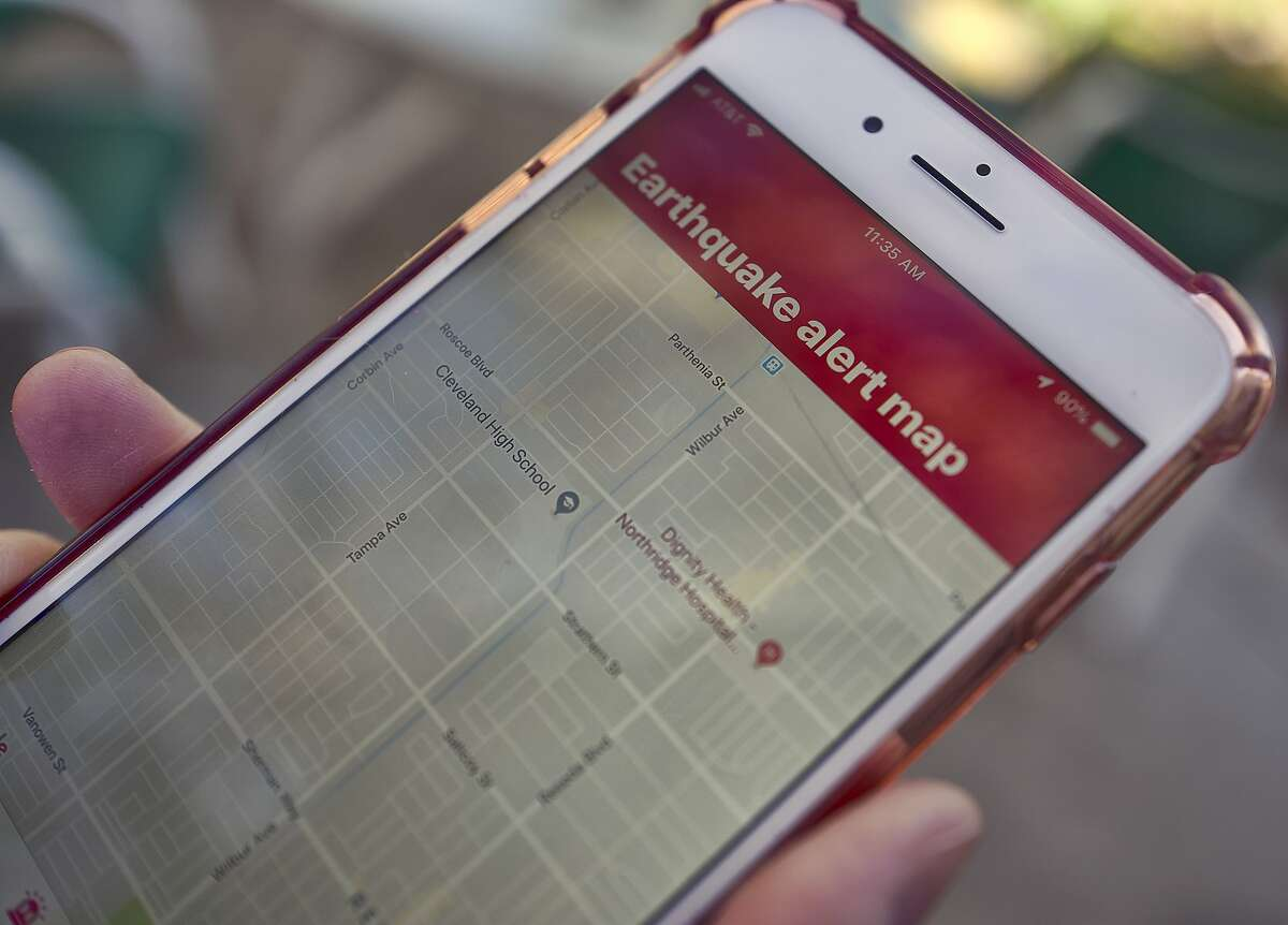 A mobile phone customer looks at an earthquake warning application on their phone in Los Angeles on Thursday, Jan. 3, 2019. Los Angeles has released the app that could give LA County residents precious seconds to drop, cover and hold on in the event of a quake. The city announced Wednesday that ShakeAlertLA is available for download on Android and Apple phones. (AP Photo/Richard Vogel)