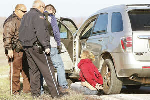 Police officers question the female occupant of a Chevrolet Equinox Thursday morning who took Alton police, and other agencies, on a more than 40-mile, high-speed chase from TheBANK of Edwardsville drive-through window in Alton to just west of the intersection of Illinois routes 16 and 100 in Jersey County, six miles from Hardin. Police received a call that the woman was allegedly trying to pass a forged check and she fled when Alton Police Sgt. William Brantley arrived and got out of his car. There was a male passenger in the Equinox, which exceeded 100 miles per hour for most of the pursuit.