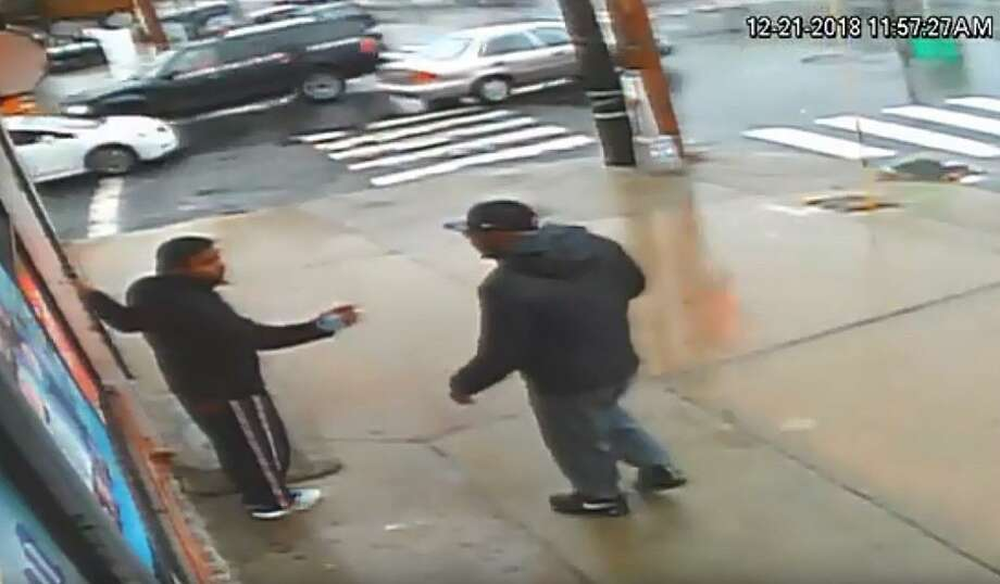 In a video provided by Bridgeport, Conn., police, the suspect (right) can be seen approaching a man standing outside the market before assaulting him. Photo: Contributed Photo / Bridgeport Police Department / Contributed Photo / Connecticut Post Contributed