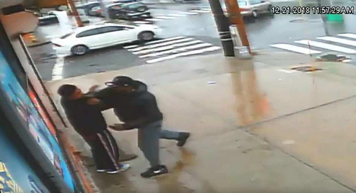 A video provided by Bridgeport, Conn., police shows the suspect (right) approach a man standing outside the market and assault him.