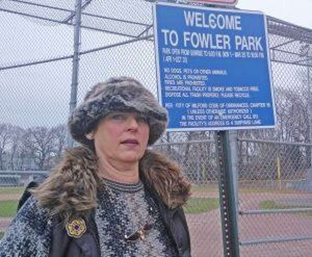 Mary Schipke stands under one of the newly posted signs, which state that people have to leave the park by 9 p.m.