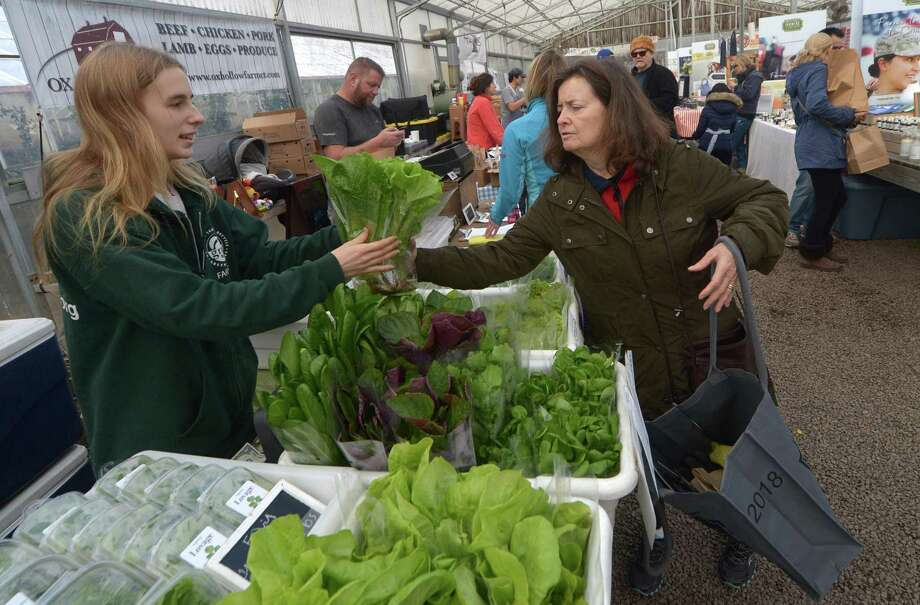 Allie Miller, from Two Guys from Woodbridge, produce sells Patricia Spuani of New Canaan some fresh lettuce during the Westport Winter Farmers Market on Dec. 29 at Gilbertie's Herbs and Garden Center in Westport. Photo: Erik Trautmann / Hearst Connecticut Media / Norwalk Hour