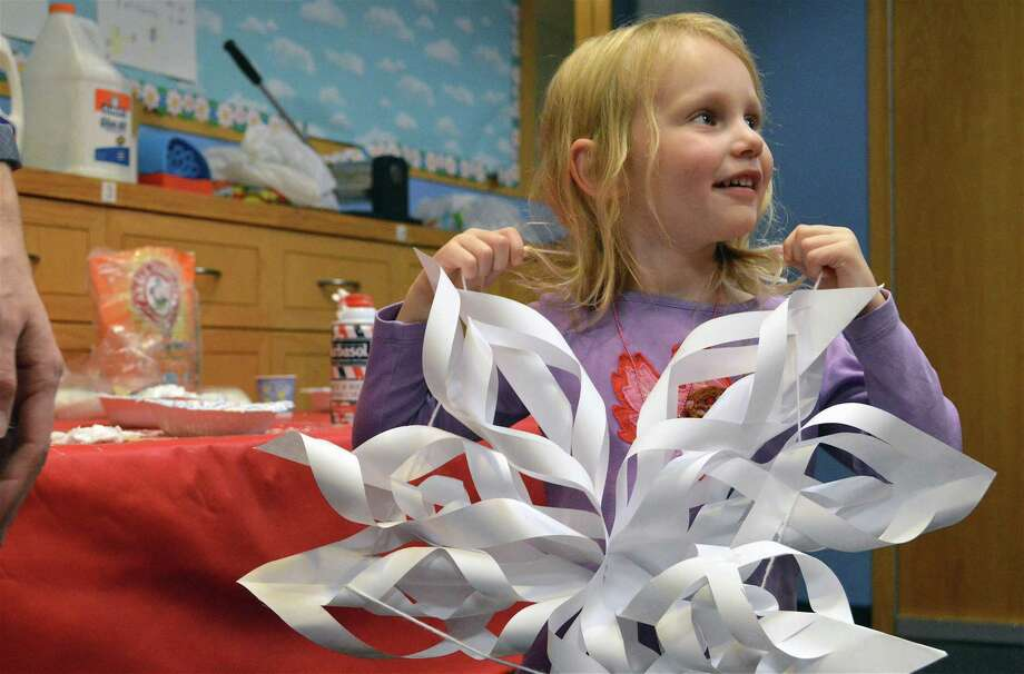 Clara Palmer, 4, of New Canaan, tries on a decoration for size at a science and art snowflake exploration program at the New Canaan Library on Dec. 28, 2018. Photo: Jarret Liotta / For Hearst Connecticut Media / New Canaan News Freelance