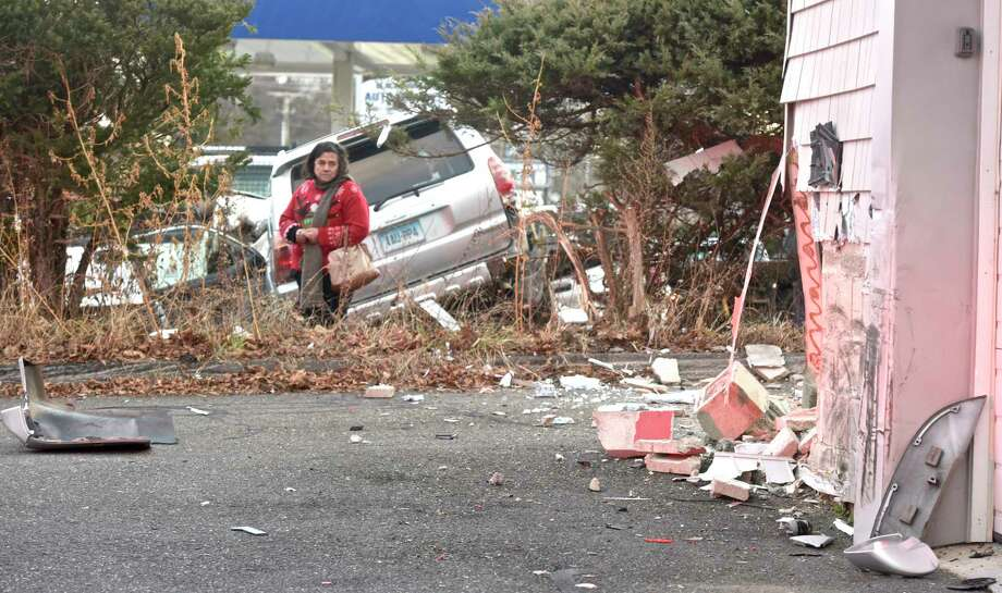 A woman looks at the damage after an SUV hit the corner of the Germantown Volunteer Fire Department took out a part of a hedge and struck vehicles at a Blackman's Auto Repair, on Germantown Road, before coming to a stop. Thursday afternoon, January 3, 2019, in Danbury, Conn. Photo: H John Voorhees III, Hearst Connecticut Media / The News-Times