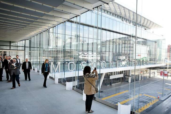 Guests take pictures from a new pedestrian walkway that connects the Moscone North and South buildings across Howard St., during a grand re-opening of the newly renovated Moscone Center in San Francisco, Calif., on Thursday, January 3, 2019.