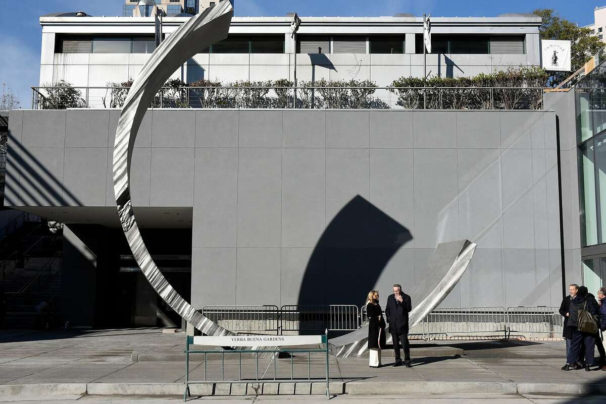 Guests stand near a large sculpture in front of the Moscone North building during a grand re-opening of the newly renovated Moscone Center in San Francisco, Calif., on Thursday, January 3, 2019.