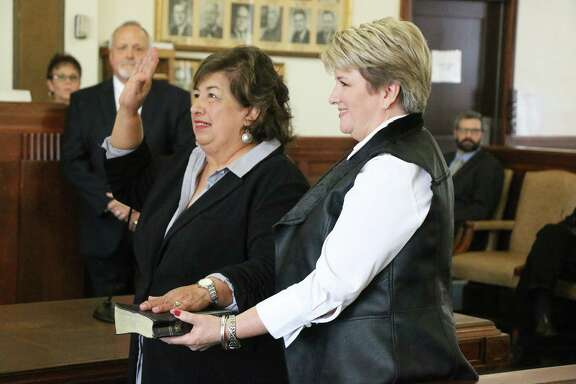 Delia Sellers is sworn in as the new District Clerk. She is using the Bible of former District Clerk Joy Kay McManus who passed away on Mar. 7, 2018. Joy Kays daughter Brenda is holding her mothers Bible for Summers.