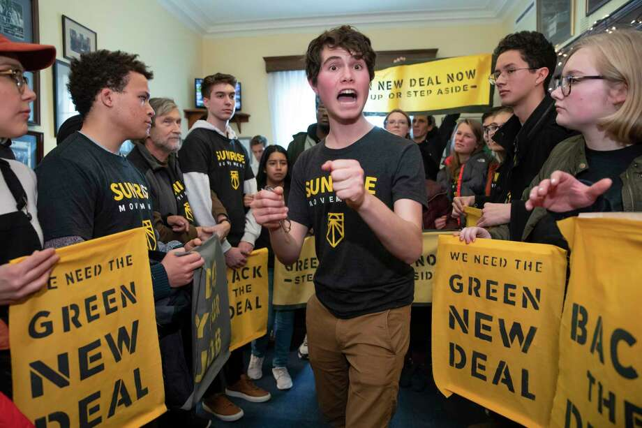Jeremy Ornstein of Watertown, Mass., center, cheers on fellow environmental activists as they occupy the office of Rep. Steny Hoyer, D-Md., the incoming majority leader, as they try to pressure Democratic support for a sweeping agenda to fight climate change, on Capitol Hill in Washington, Monday, Dec. 10, 2018. (AP Photo/J. Scott Applewhite) Photo: J. Scott Applewhite / Copyright 2018 The Associated Press. All rights reserved