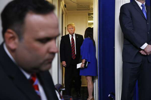 Sarah Huckabee Sanders opens the door for President Donald Trump as he arrives in a surprise appearance at the press briefing room, Thursday Jan. 3, 2019, to speak about border security at the White House in Washington. (AP Photo/Jacquelyn Martin)