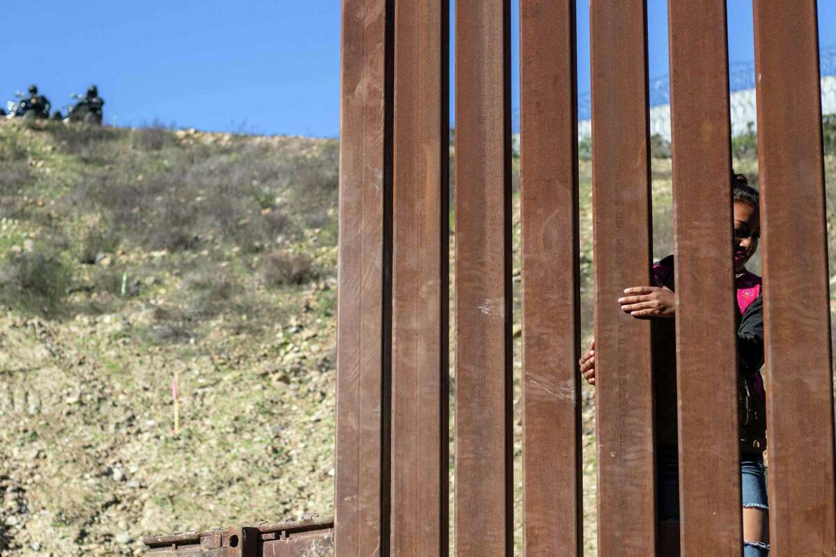 US border patrol officers watch as a 17-year-old Honduran migrant crosses the U.S.-Mexico border fence from Tijuana to the U.S., on Dec. 30. Trump's insistence on a wall is a symbol of futitility.