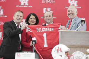 University of Houston's new head football coach, Dana Holgorsen, second from left, holds jersey after his introductory press conference withTilman Fertitta, from left, Renu Khartor and Chris Pezman on Thursday, Jan. 3, 2019 in Houston.