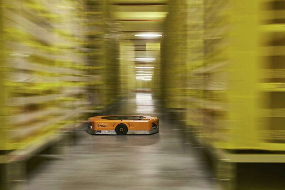 Bloomberg Best of the Year 2018: An automated transport robot moves between shelving units containing goods at Amazon.com Inc.'s new fulfillment center in Kolbaskowo, Poland, on Friday, Feb. 16, 2018. Photographer: Bartek Sadowski/Bloomberg Photo: Bartek Sadowski / Bloomberg / © 2018 Bloomberg Finance LP