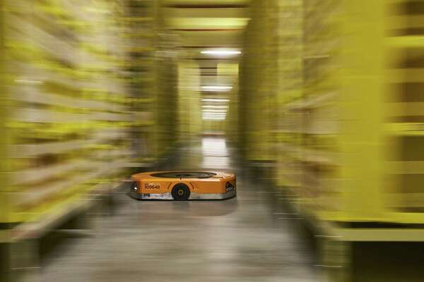Bloomberg Best of the Year 2018: An automated transport robot moves between shelving units containing goods at Amazon.com Inc.'s new fulfillment center in Kolbaskowo, Poland, on Friday, Feb. 16, 2018. Photographer: Bartek Sadowski/Bloomberg