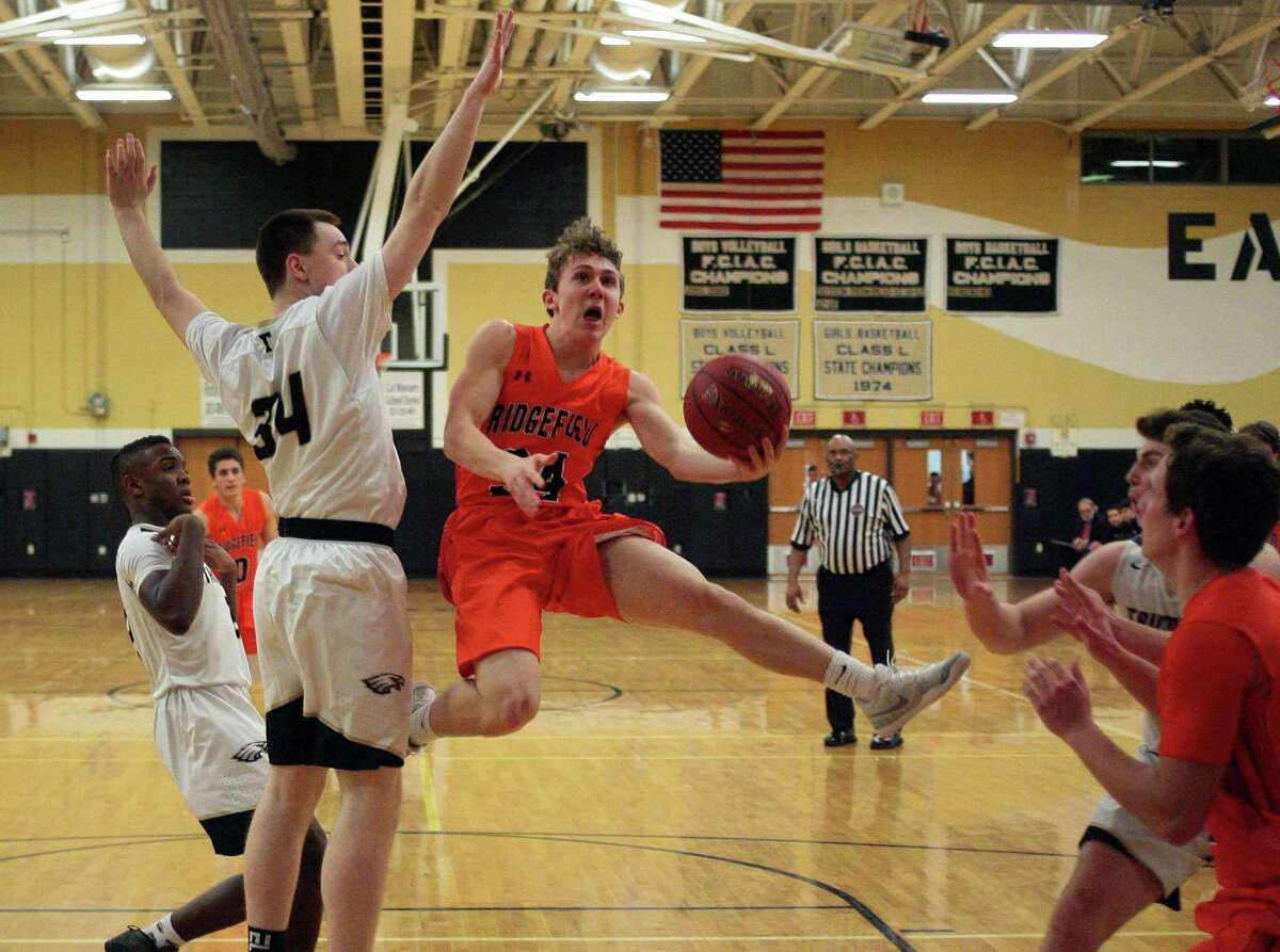 Ridgefield's James St. Pierre (34) attempts a layup as Trumbull's Evan Gutowski (34) defends on Thursday.